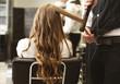 Hairdresser Making Curls With Straightener To Client's Hair In Salon