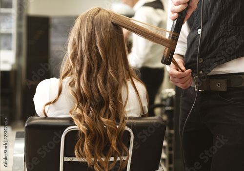 Hairdresser Making Curls With Straightener To Client's Hair In Salon