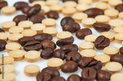 Leinwand Poster Coffee beans mixed with caffeine tablets are scattered on a light surface