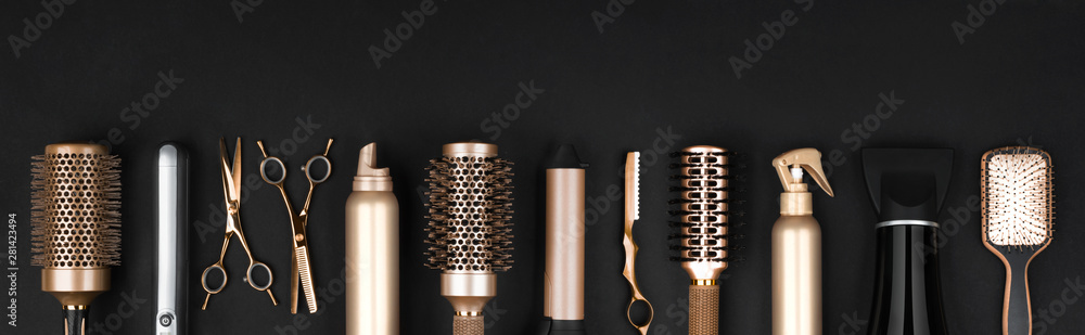 Fototapeta Collection of professional hair dresser tools arranged on dark background