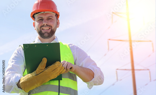An electrician in the fields near the power transmission