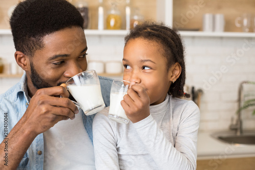 Obraz na plátně Black girl and her father drinking fresh milk