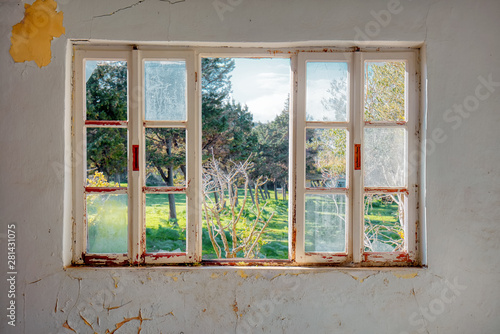 Vintage wooden window frame with broken glass looking through a green meadow field. of an Interior of a desolated house with dirty cracked wall.
