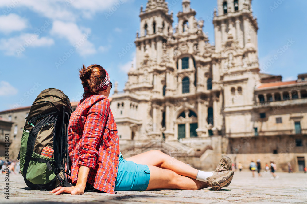 Fototapety, obrazy: Young female backpacker piligrim sitting on the Obradeiro square (plaza) in Santiago de Compostela