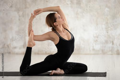 Fototapeta Woman performing One-Legged King Pigeon Pose on yoga mat obraz na płótnie