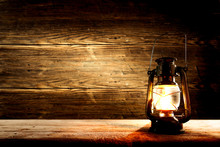 A Burning Lantern On Wooden Background.