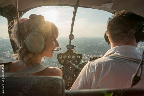 Valokuvatapetti Portrait of beautiful blonde women and pilot enjoying helicopter flight