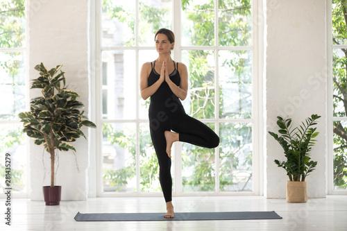 Yogini beautiful woman practise yoga performs Tree pose asana indoors Canvas Print