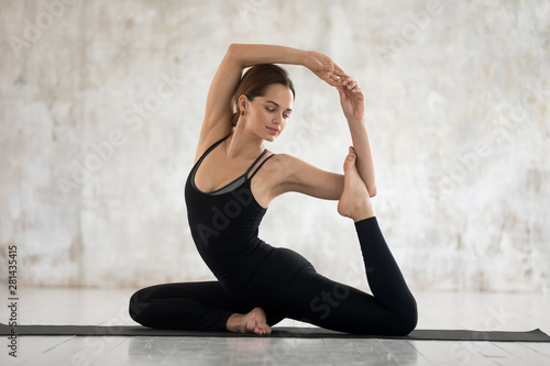 Beautiful woman performs Mermaid Pose deep backbend asana yoga Wallpaper Mural
