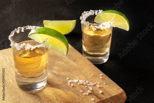 Golden tequila shots with salt and lime slices on black, with a place for text Wallpaper Mural