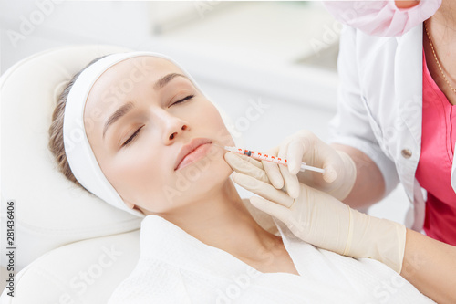 Poster Spa Close-up master cosmetologist makes injection of hiluronic acid in the face of a beautiful young woman. The concept of modern anti-aging procedures in the beauty salon