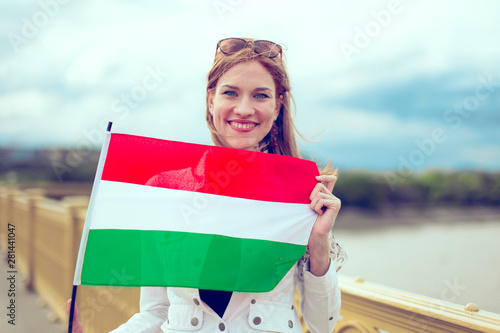 Fotomural Young redhead woman holding Hungarian flag on bridge