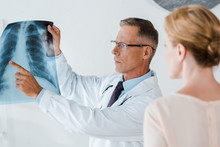 Selective Focus Of Serious Doctor In Glasses Pointing With Finger At X-ray Near Woman