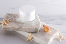 Cosmetic Glass Jar On The White Stones And Seashells.Mineral Moisturizing Cream