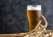 Misted Glass Of Light Beer On A Wooden Table And Wheat