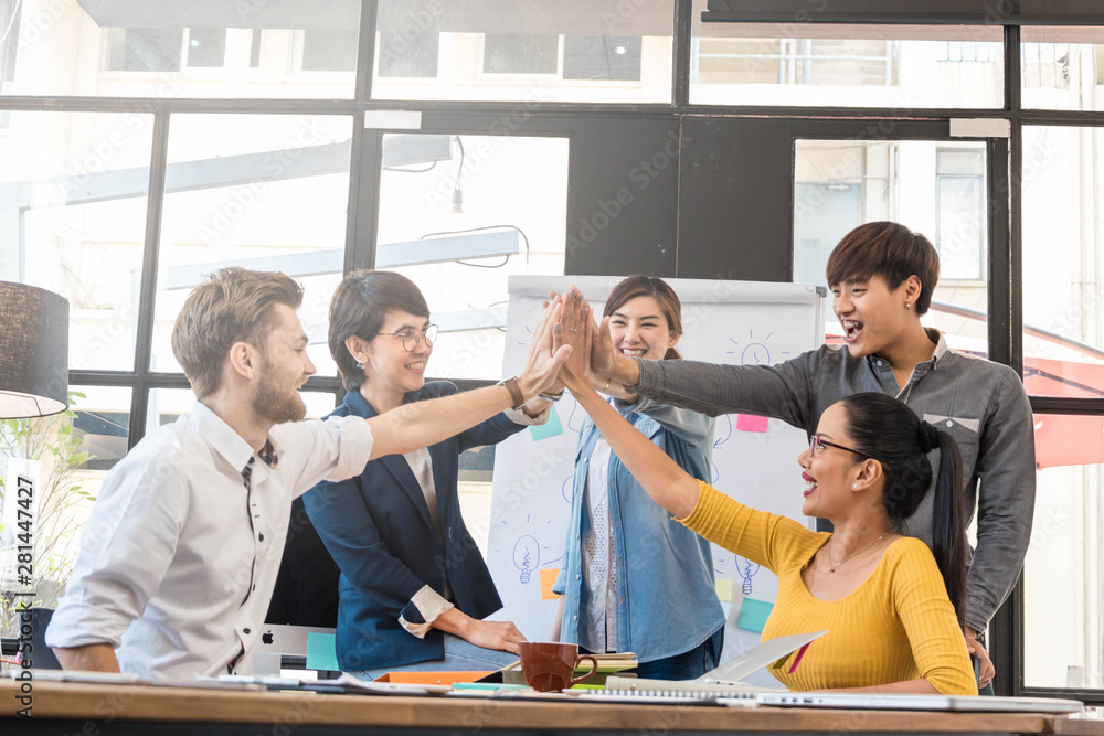 Fototapeta Group of five creative workers giving each other high-five with big smile on face, successful team performance, finishing touch