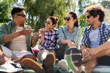 Leisure, Picnic And People Concept - Friends Hanging Out And Talking Outdoors In Summer Park