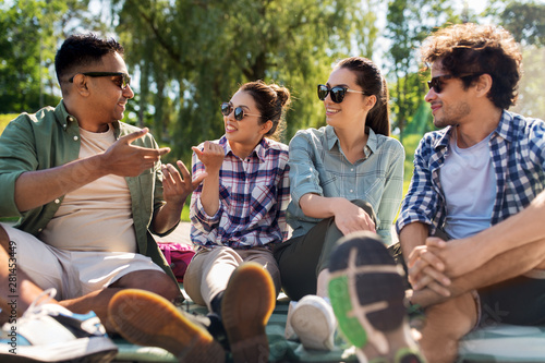 Foto  leisure, picnic and people concept - friends hanging out and talking outdoors in