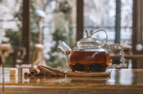 Recess Fitting Tea tea with cinnamon in a teapot on a wooden table.
