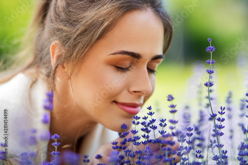 Fototapeta gardening and people concept - close up of happy young woman smelling lavender flowers at summer garden obraz