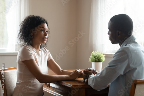 African couple sitting at table having heart-to-heart talk Canvas Print