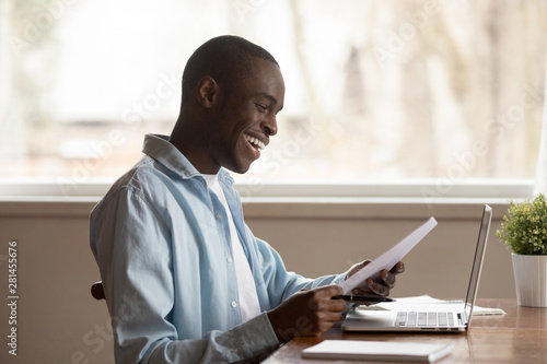 Fototapeta African guy sit at table read documents feels happy obraz