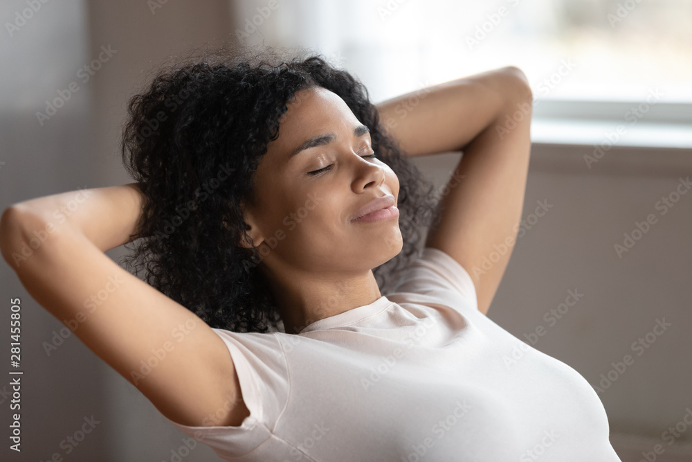 Fototapety, obrazy: Mixed race woman putting hands behind head resting indoors