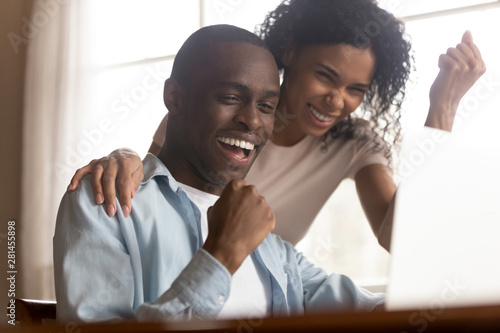 Fotografía  African couple look at computer feels excited celebrating lottery win