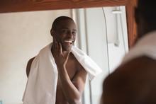 Shaved Handsome African Man Looking In Mirror Feels Satisfied