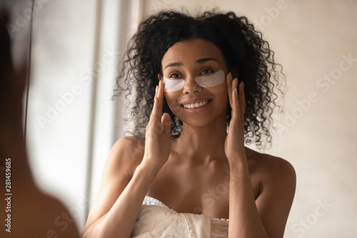 Attractive african woman applied under-eye patches looking in mirror Fototapet