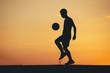 Leinwanddruck Bild - Silhouette of a man playing soccer in golden hour, sunset.