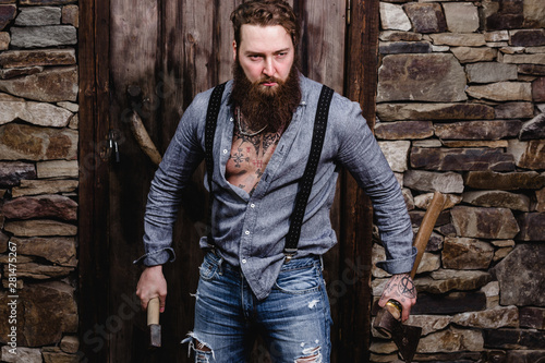 Strong brutal man with a beard and tattoos on his hands dressed in stylish casua Fototapet