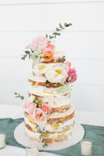 Naked Wedding Cake Decorated With Gold Foil And Flowers, Three Tiered Cake, White Background, Copy Space