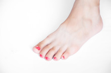 The Left Leg Of A Woman. Nails Are Painted Red. On A White Background