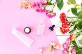 Fototapeta Kawa jest smaczna - Skin Care Cosmetics in a Frame of Fresh Roses. Essence, Oil on a pink and white desk.