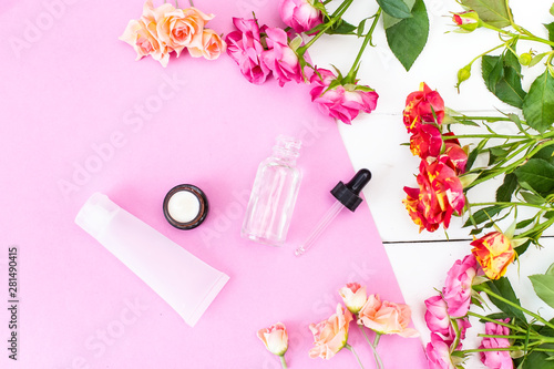 Skin Care Cosmetics in a Frame of Fresh Roses. Essence, Oil on a pink and white desk.