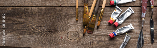 top view of oil paints in tubes, paintbrushes and spatulas on wooden surface wit Wallpaper Mural