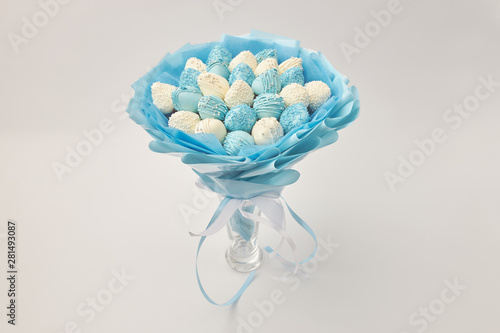 Cuadros en Lienzo Delicious bouquet of strawberries covered with white and blue chocolate on a whi