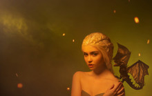 Young Woman With White Braided Hair And Little Dragon On Shoulder. Hostess Of Magical Beasts With Innocent Face In Fog And Sparks Of Fire, Creature Of Polymer Clay, Creative Photo. Space For Text