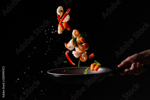 Fotografía  close-up, Seafood, chef cooks shrimps with pepper, spiked beans and Brussels sprouts in a frying pan