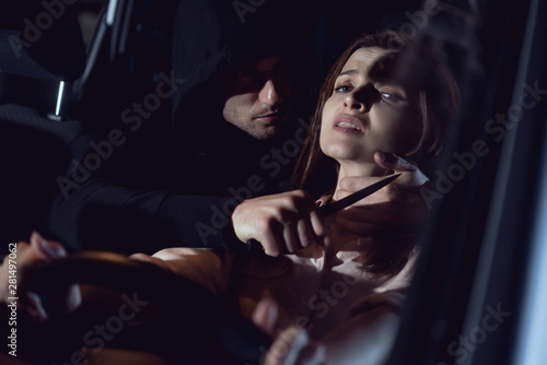 thief strangling beautiful frightened woman in automobile at night with knife Fototapet