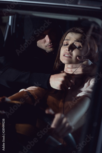 thief strangling beautiful scared woman in automobile at night with knife Fototapet