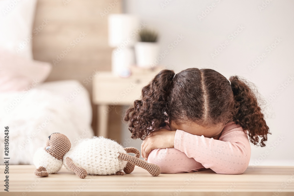 Fototapety, obrazy: Sad little African-American girl sitting at table