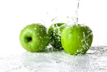 Pouring Of Water On Apples Against White Background