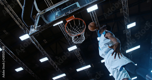 Low angle of professional basketball player in action performing slam dunk in a basketball hoop on a sports arena