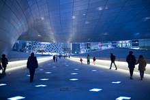 People Walking Underneath Curved Ceiling Of Building