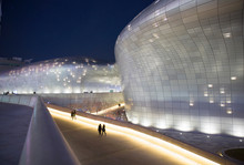 People Walking By Modern Illuminated Building At Night
