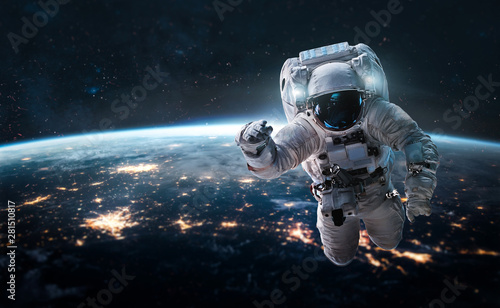 Obraz Astronaut in the outer space over the nightly planet Earth. City lights. Abstract wallpaper. Spaceman. Elements of this image furnished by NASA - fototapety do salonu