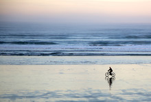Side View Of Man Riding Bicycle On Beach