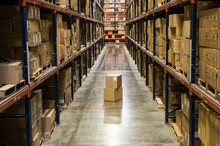 Racks Of Cardboard Boxes In Distribution Warehouse